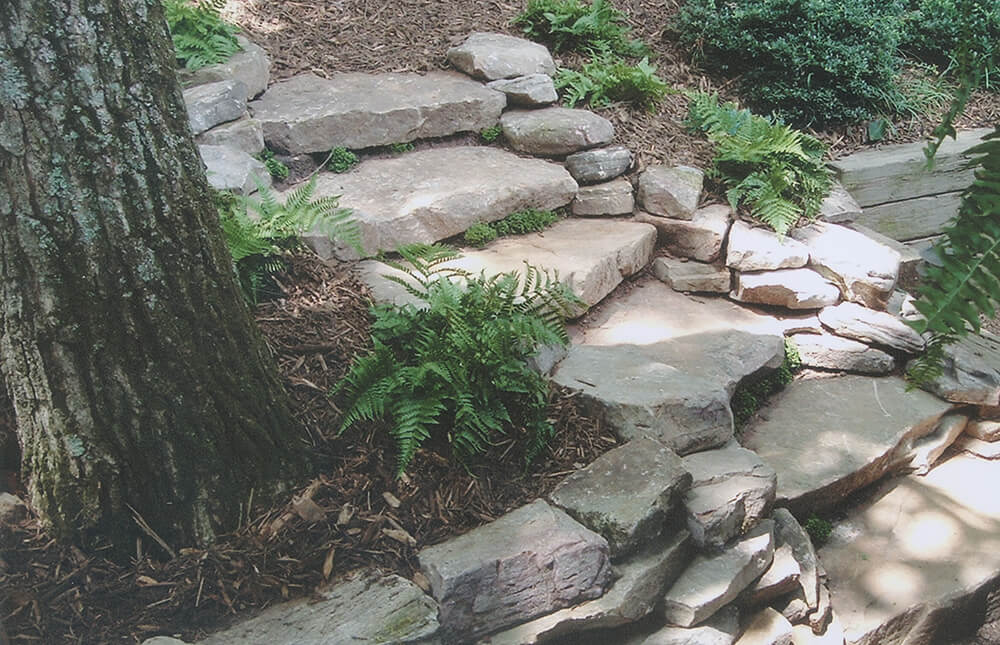 Mulched planting beds flanking stone walkway
