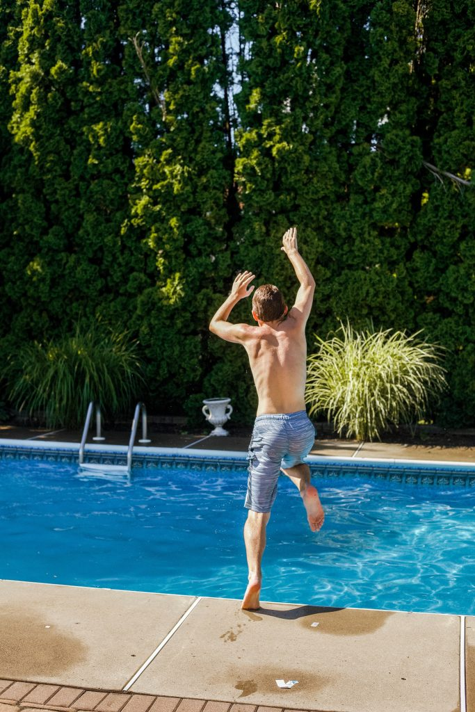 Boy jumping into pool surrounded by plants
