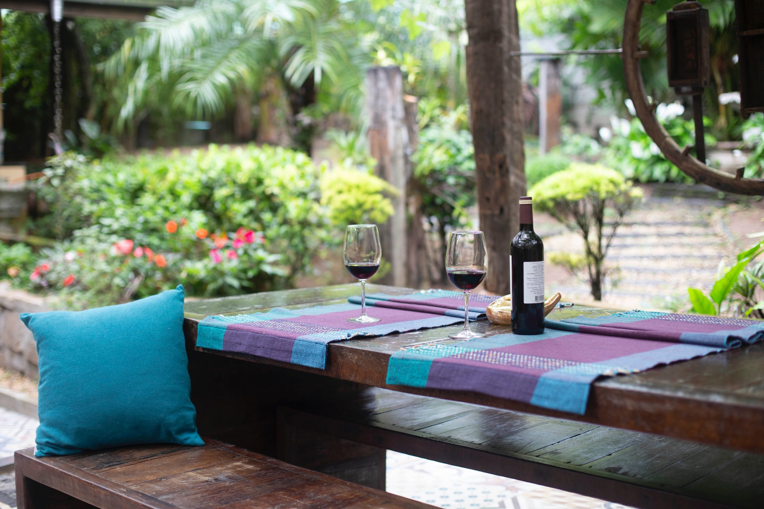 Table and benches with wine bottle and glasses in landscaped patio